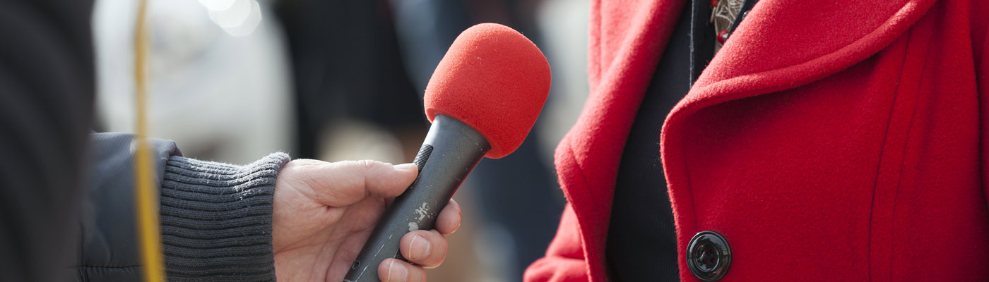 Woman speaking into press microphone