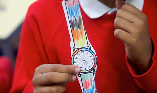 Primary school child showing off their handmade paper wristwatch.