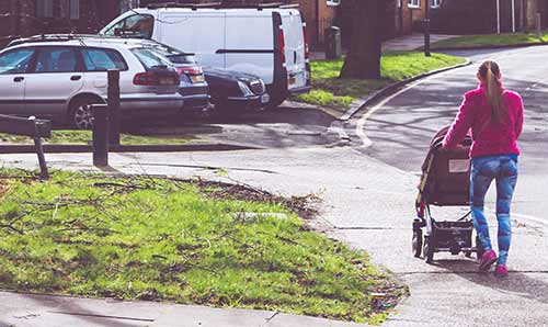 Young woman pushing pram through housing estate.