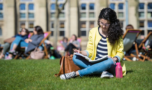 Student sat on the grass reading a book