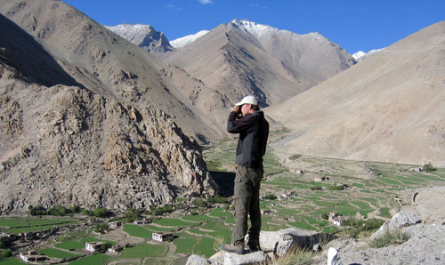 Photograph of a hiker looking down from a hillside on a village